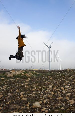 Girl Jumping Near To Some Mills Wind