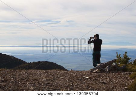Man Taking A Photo Of A Foggy Landscape