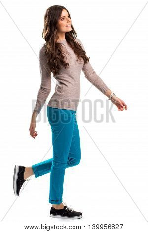 Girl in sweater is walking. Turquoise pants and sneakers. Model cheerfully smiles. Natural wool and cotton.