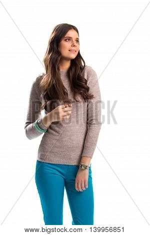 Lady in beige pullover. Turquoise pants and watch. Dreaming woman on white background. How to dress trendy.