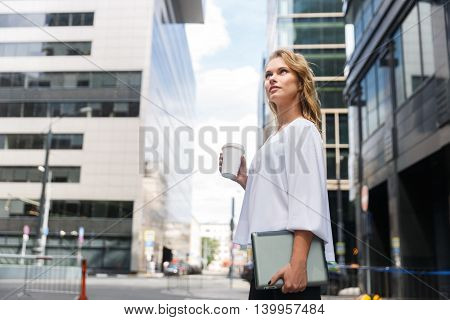 Young blond businesswoman with coffee takeaway on blurred urban street background