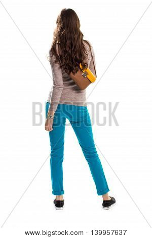 Lady in turquoise pants. Back view of beige pullover. Sneakers from spring collection. Two tone leather bag.