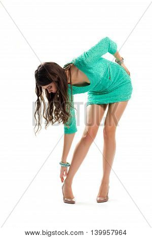 Woman in dress touches leg. Short turquoise dress and heels. New pair of evening shoes. Look like a model.
