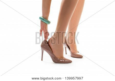 Woman's hand touches heel shoe. Legs in beige heels. Size that fits perfectly. Shoes for casual evening outfit.