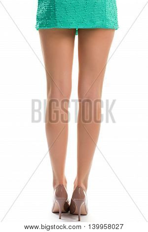 Woman's legs in glossy shoes. Back view of beige heels. New footwear of high quality. Attractive legs of young model.