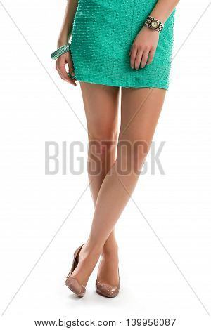 Legs in beige heel shoes. Short dress and small watch. Fashionable evening apparel. Look charming this spring.