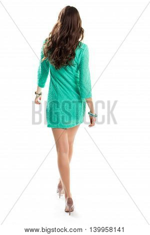 Girl in dress is walking. Back view of short dress. Date outfit with expensive footwear. Stay charming and confident.
