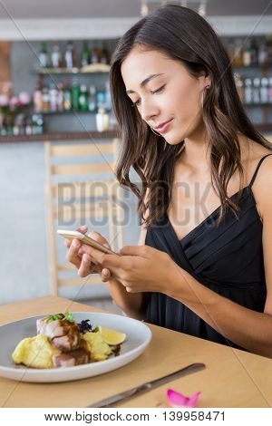 Woman using mobile phone while having meal