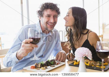 Woman whispering on mans ear in restaurant
