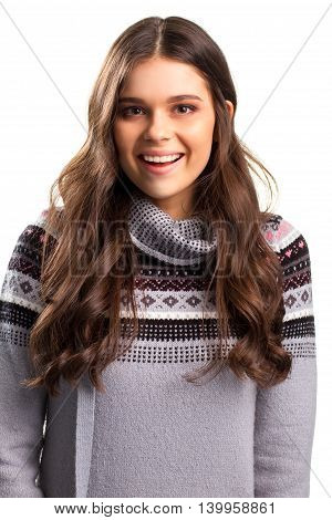 Smiling face of young lady. Gray sweater with pattern. Expression of joy. Cheerful model looks at camera.