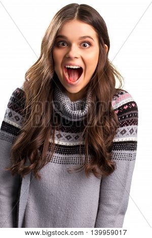 Excited woman in gray sweater. Girl with wide open mouth. Feeling of triumph. Can't hide the joy.