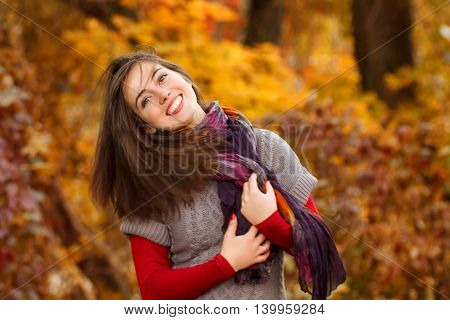 Portrait of beautiful smiling young woman in autumn park. Smiling happy girl portrait in autumn. Concept autumn
