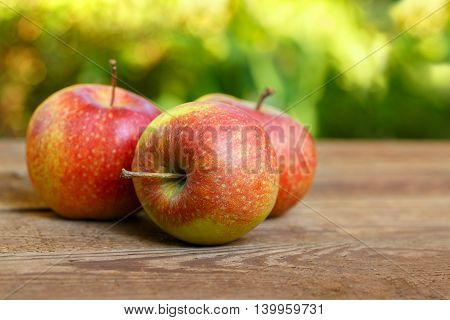 red apples on a wooden tabletop outdoors with copyspace. Apples on wooden table over garden bokeh background. Ripe apples on table outdoors