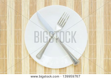 Closeup white ceramic dish with stainless fork and knife on wood mat textured background on dining table in top view in unfinished eating concept