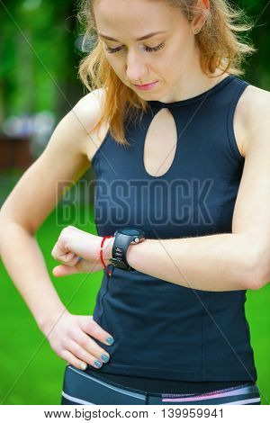 Female Runner Looking At Her Sport Watch.