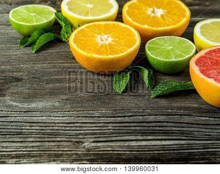 Photo of a sliced grapefruit orange lemon lime and mint leaves on a old rustic slab of barn board.