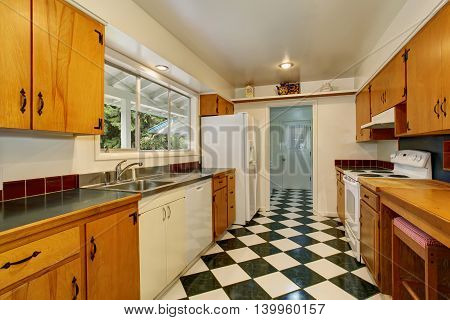 Narrow Kitchen Room Interior With Light Brown Cabinets, White And Black Tile