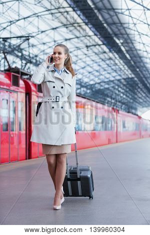 Businesswoman with luggage at the station