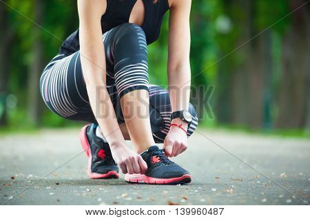 Closeup Young Woman Tying Her Laces Before A Run.