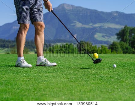 Photo of a male golfer teeing off on a golf course on a beautiful day.