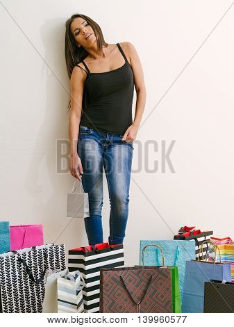Photo of a tired young woman standing around all her shopping bags.