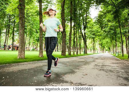 Full Length Portrait Of A Female Runner Running In The Park.
