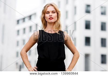 Outdoors portrait of confident business woman with blonde curly hair, red lipstick and blue eyes