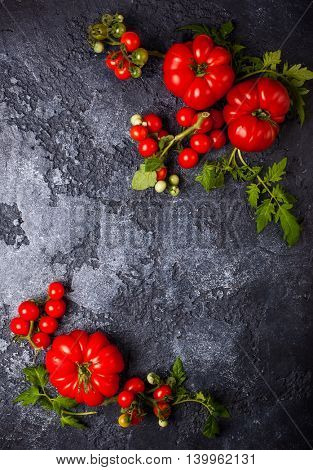 Various fresh tomatoes with green leaves on a black background