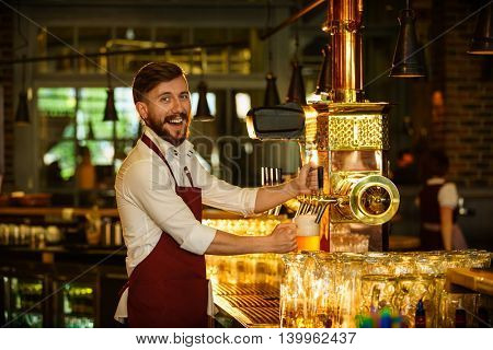 Smiling bartender pours a beer indoors