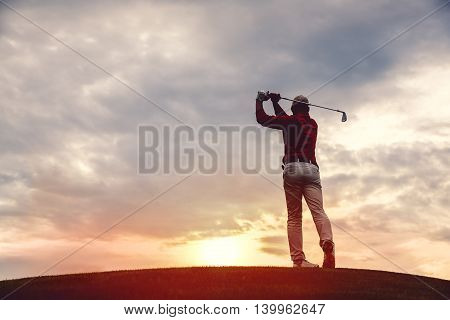 silhouette of man golfer with golf club at sunset. back view