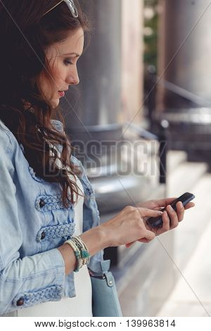Portrait in profile brunette woman touching screen her smartphone outdoors