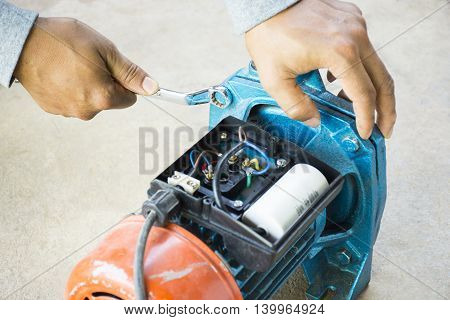 Electric motor  and man working equipment repair on cement floor background. Background motor or equipment.