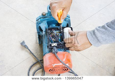 Electric motor  and man working equipment repair on cement floor background.Background motor or equipment.