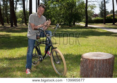 Gorgeous Man Talking On Cell Phone Holding His Cycle.