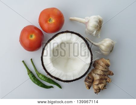 Top View of Coconut,Ginger ,Tomatoes,Garlic and Green Chili on White Background