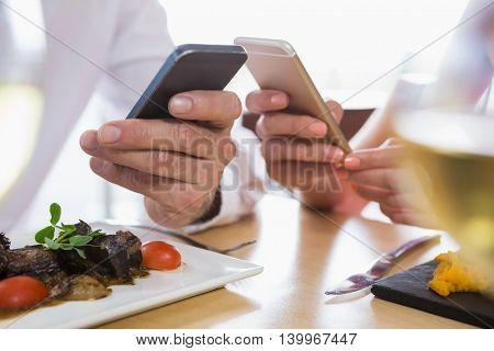 Couple using mobile in restaurant