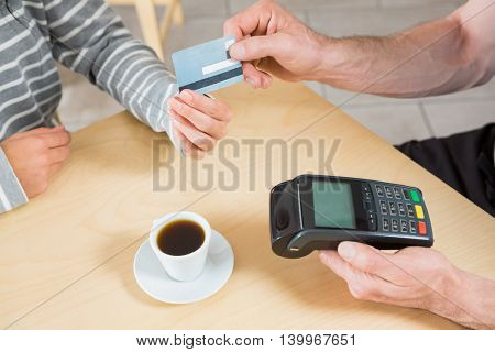 Woman making payment through credit card in cafeteria