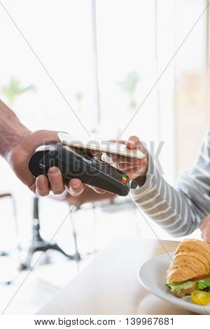 Woman making payment through NFC in cafeteria