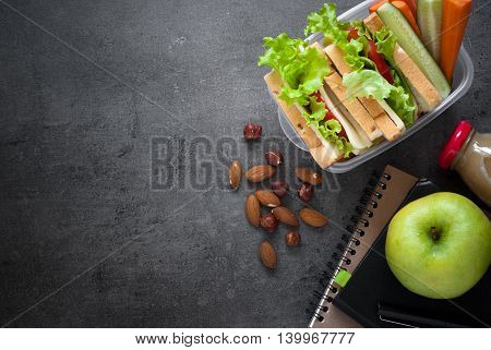 Lunch box with sandwich vegetables juice nuts and apple on black background. Healthy eating. Flat lay.