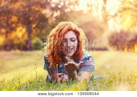 Girl with red curly hair and blue floral dress lying on her stomach in the park and looking at the palm of her hand. Plenty of copy space