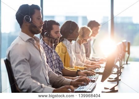 Team of colleagues working at their desk with headset in the office