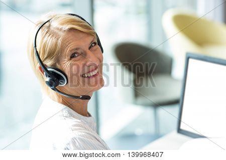 Portrait of a woman working on computer with headset in office