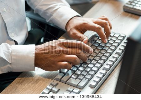 Close-Up of man using computer keyboard in the office