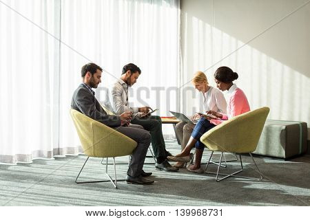 Business people using mobile phone, digital tablet and laptop in the office