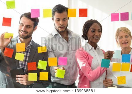 Business people sticking adhesive notes on glass wall in the office