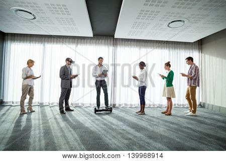 Business people using electronic gadgets in the office