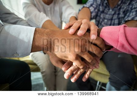 Mid section of business people with hand stacked during meeting in the office