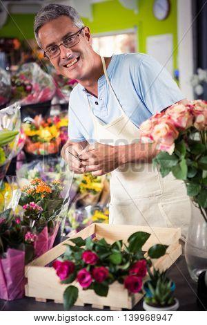 Portrait of male florist preparing bouquet of flower at his flower shop