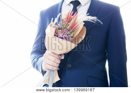 Man In Suit Holding Bouquet With Over Exposed White Rim Light From Behind
