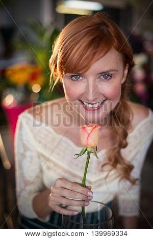 Portrait of female florist smelling a rose flower in the flower shop